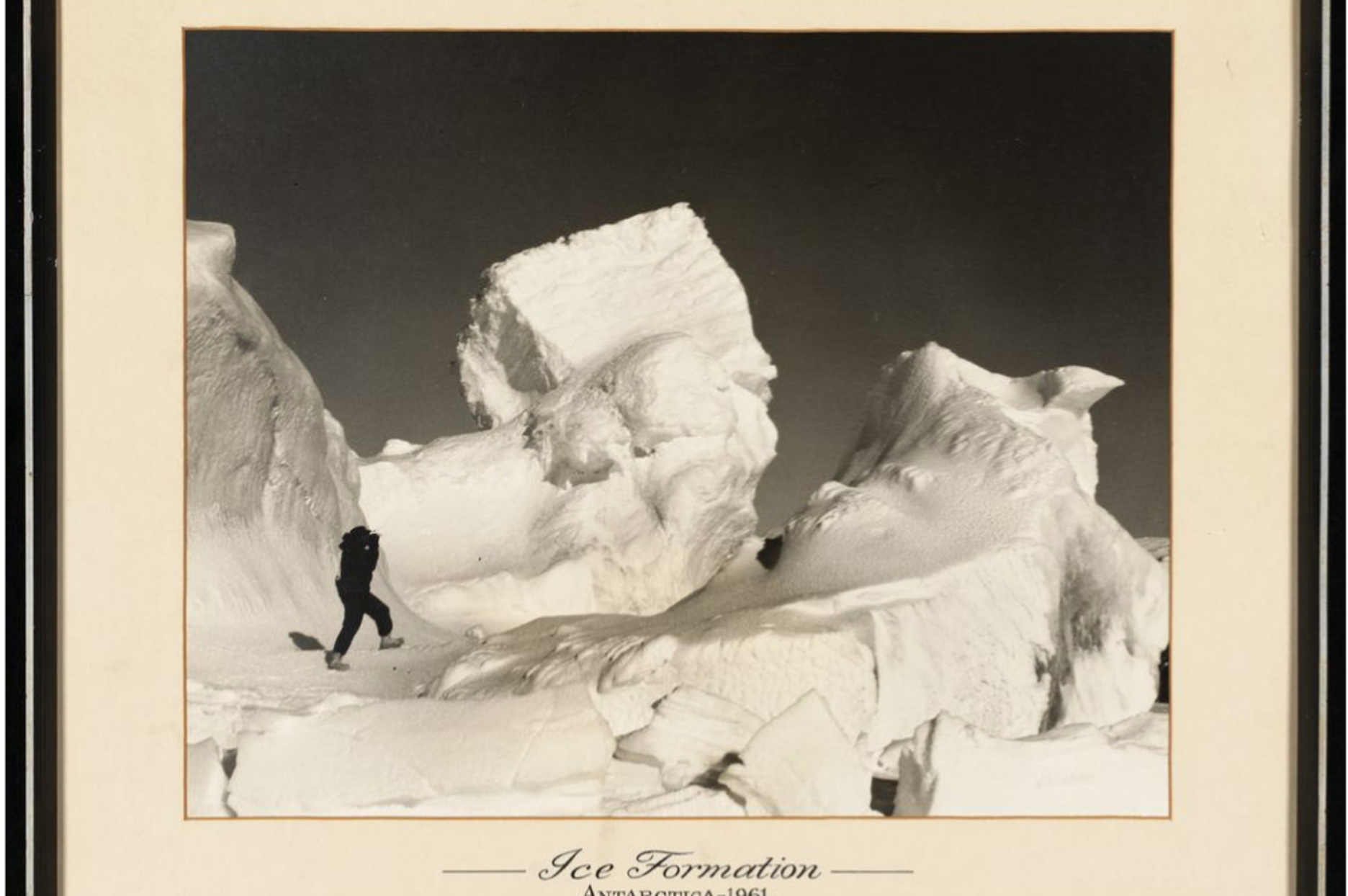 14587 1 An unidentified figure stands next to an ice formation in Antarctica 1961